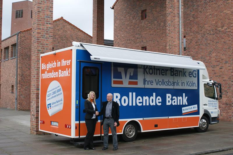 Ina Siebel, Beraterin und Fahrerin der Rollenden Blumenberg begrüßt vom Kaplan Alfons Holländer. (Foto: Kölner Bank)